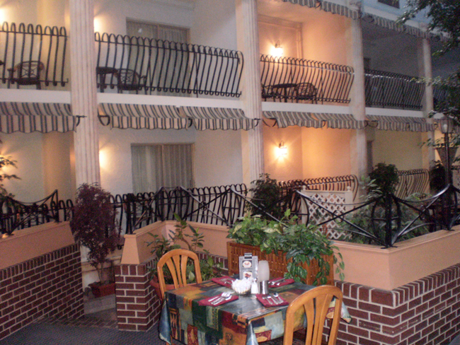 Indoor Courtyard with restaurant table and brick half wall.