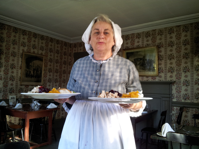 Waitress in period dress serving Thanksgiving Dinner.