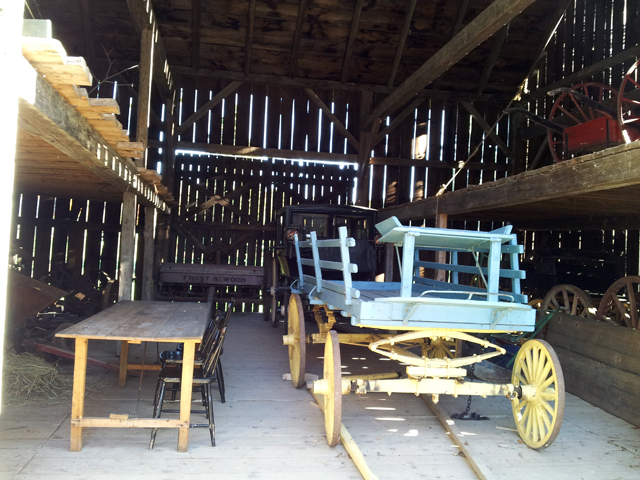wagon and carriage and tableand chairs inside a barn