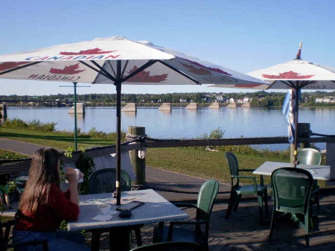 Woman at a table enjoying a beautiful view of the St John River.